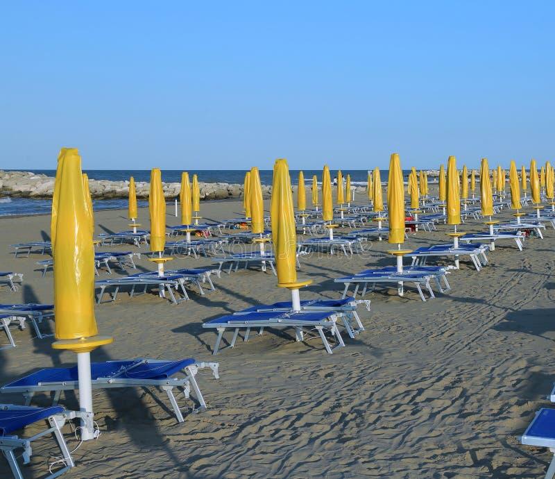 Gula solparaplyer på havsstranden med dagdrivare royaltyfri foto
