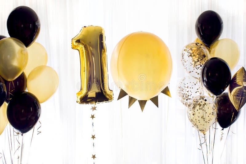 Gula svarta heliumballonger nummer tio 10 arkivfoto