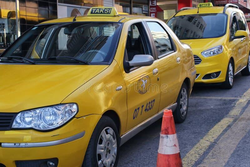 Gula taxiställningar av sidan av den väntande på passageraren för väg royaltyfri foto