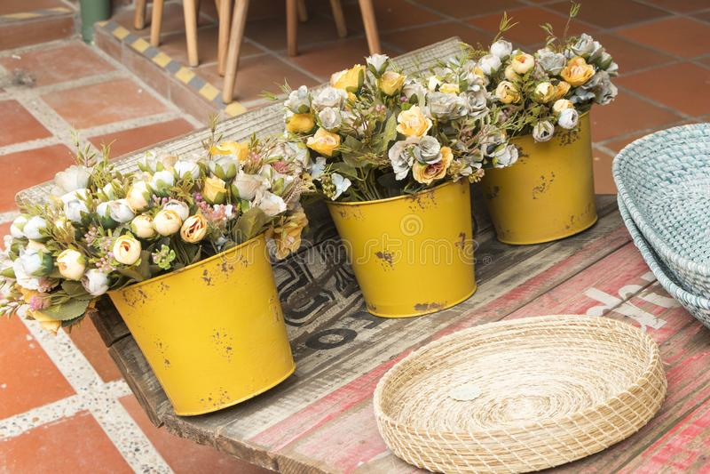 Gula tennvaser med konstgjorda blommor i gammal vagn arkivbild