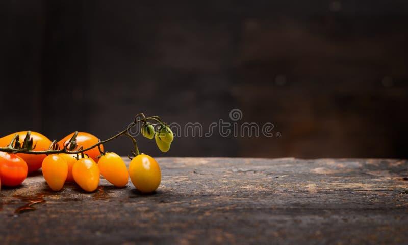 Gula tomater förgrena sig på den lantliga tabellen över mörk träbakgrund, sund mat arkivbild