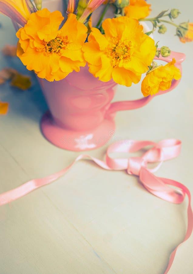 Gula trädgårds- blommor i rosa färgkopp och band royaltyfria foton