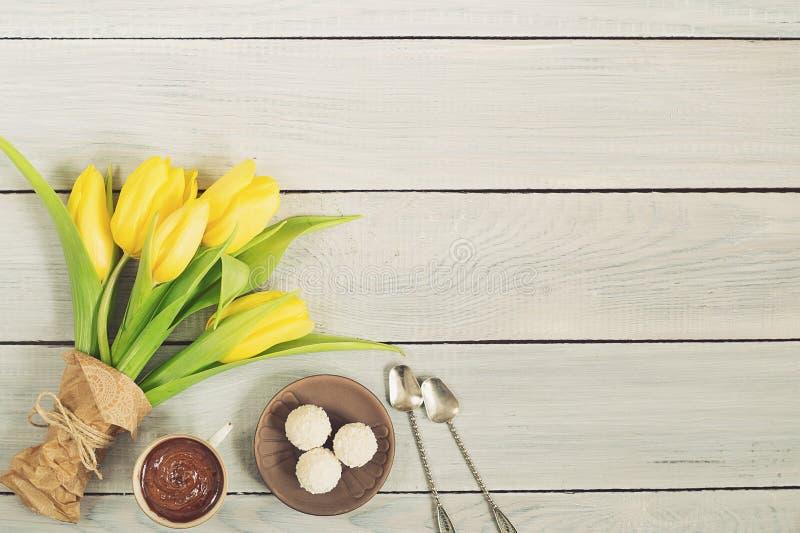 Gula tulpan, choklad och godisar på den vita trätabellen arkivfoton