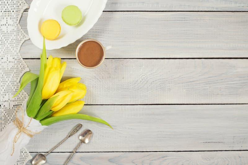 Gula tulpan, choklad och macarons på den vita trätabellen arkivfoton
