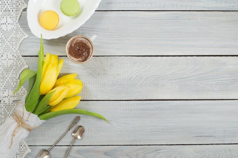 Gula tulpan, choklad och macarons på den vita trätabellen royaltyfri fotografi