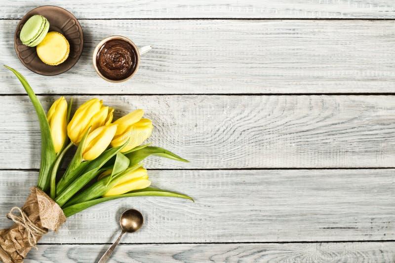 Gula tulpan, choklad och macarons på den vita trätabellen arkivfoto