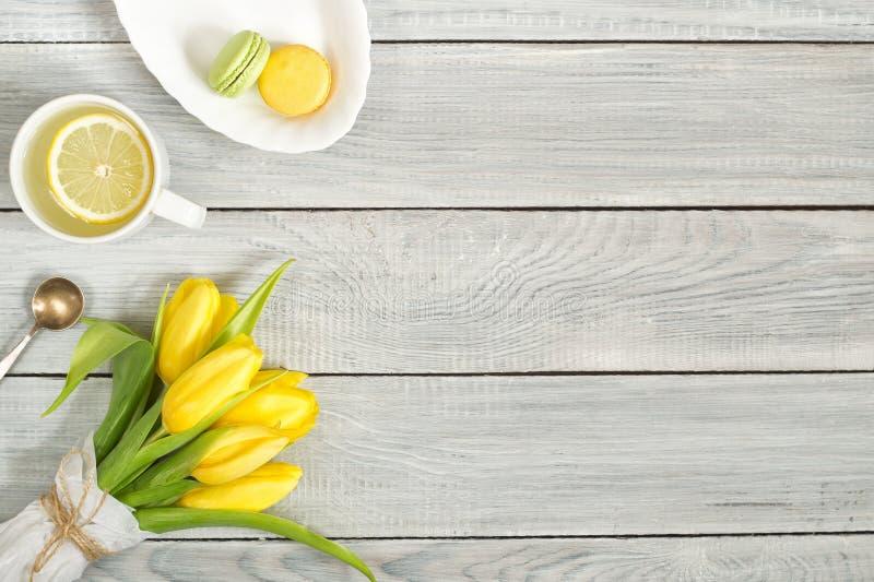 Gula tulpan, citronte och macarons på den vita trätabellen arkivbilder