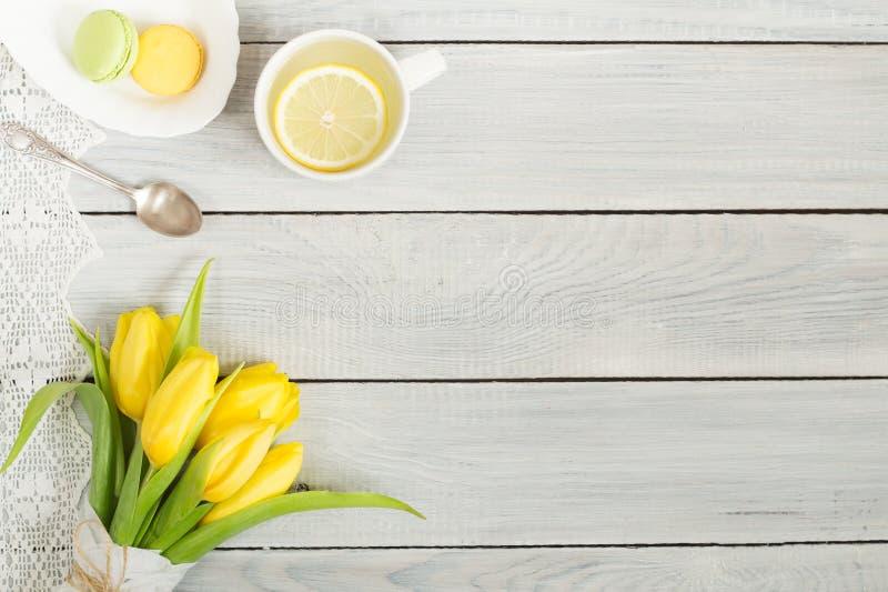 Gula tulpan, citronte och macarons på den vita trätabellen royaltyfri bild