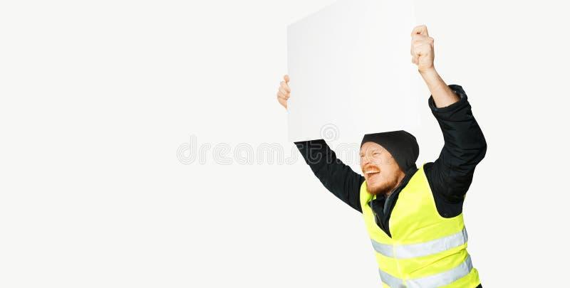 Gula västar för protester Den unga mannen rymmer en affisch på isolerat royaltyfria foton