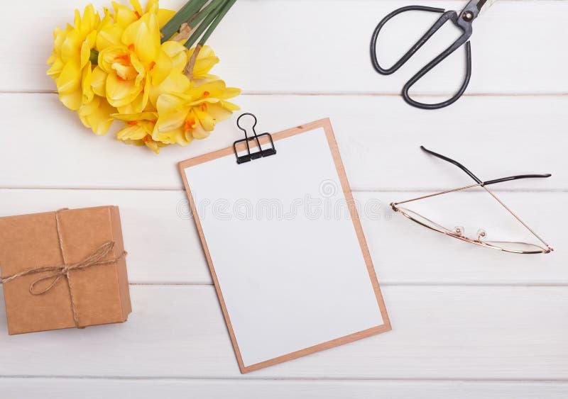 Gula vårblommor och skrivplatta med tomt papper på den vita trätabellen arkivfoto