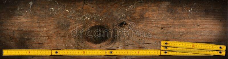 Gula vecklinjaler av trä på en arbetstabell med kopieringsutrymme royaltyfri fotografi