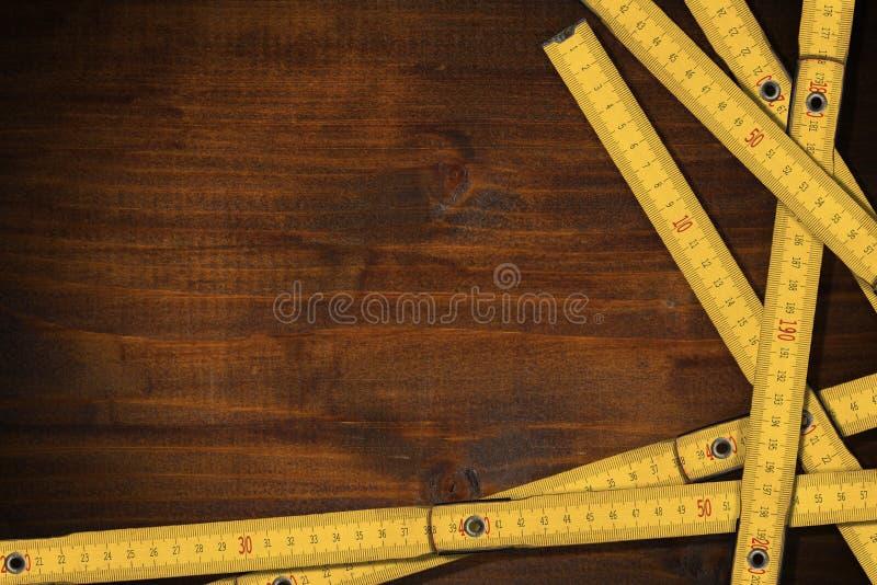 Gula vikbara linjaler av trä på en arbetstabell med kopieringsutrymme royaltyfri bild