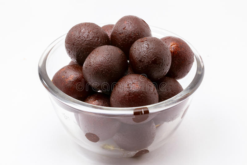 Gulab Jamun - An Indian sweet dish. Gulab Jamun in a Glass Bowl - An Indian sweet dish, round shaped, black or brown texture served after meals directly or with stock photo