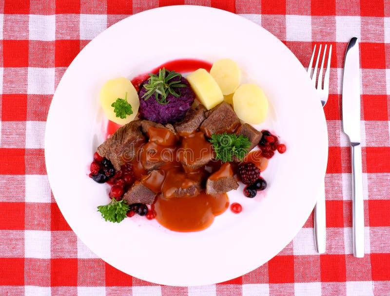 Gulasch för röda hjortar med potatisen, Bourgognesås och lösa bär royaltyfri fotografi