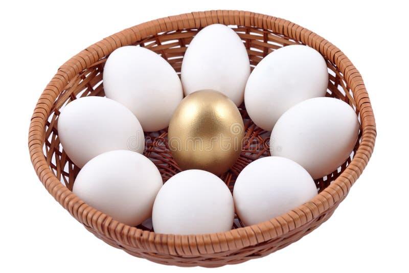 Guld- ägg- och jastägg i vide- bunke på en vit royaltyfria bilder