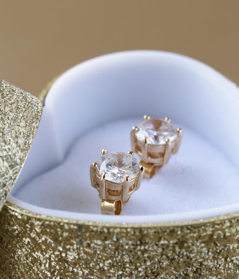 Guld- örhängen dubbar med diamanter royaltyfri foto