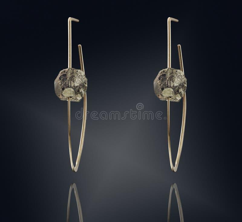 Guld- örhängen med gemstonen som isoleras på svart bakgrund arkivfoton