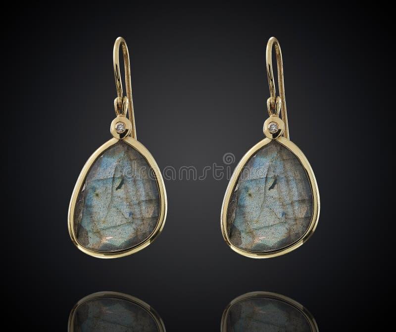 Guld- örhängen med gemstonen som isoleras på svart bakgrund royaltyfri fotografi