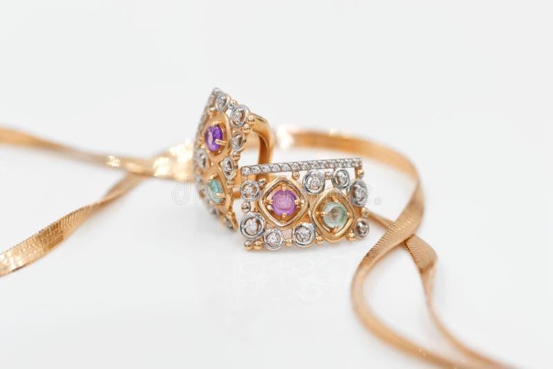 Guld- örhängen med liten gemstonesnärbild ligger med en guld- chai royaltyfri foto