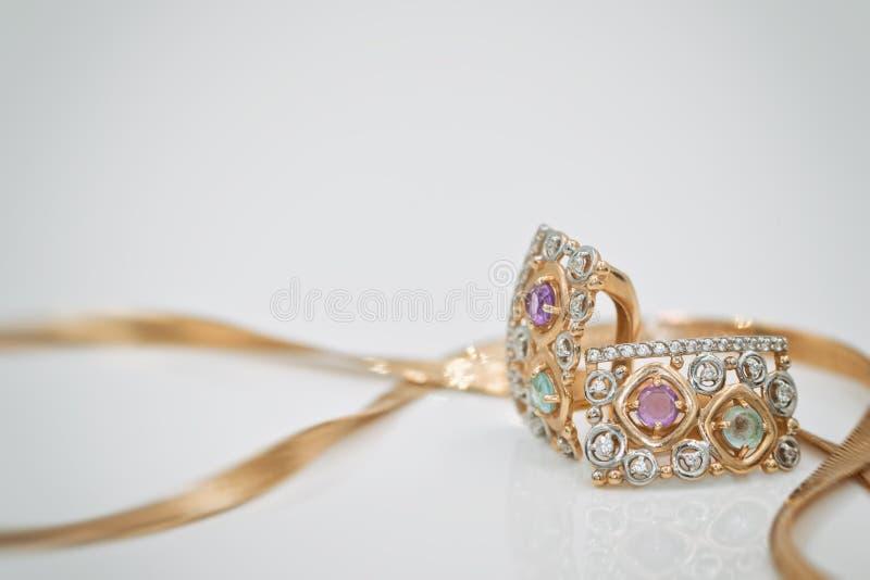 Guld- örhängen med liten gemstonesnärbild ligger med en guld- chai royaltyfri bild