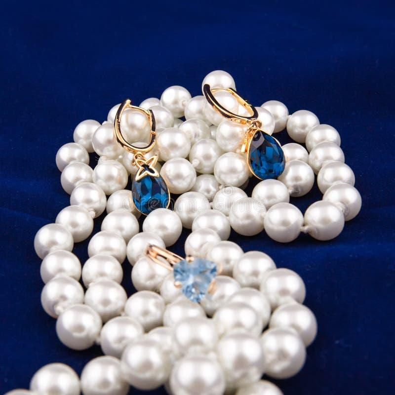 Guld- örhängen och pärlemorfärg halsband på blå bakgrund arkivfoto