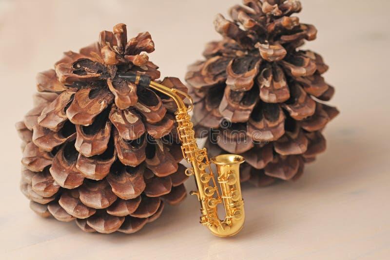 Guld- alt- saxofon- och cederträkottar invitation new year arkivfoto