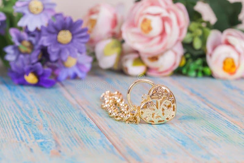 Guld- armband med hjärta på färgträ royaltyfria bilder