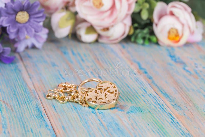 Guld- armband med hjärta på trä royaltyfri bild