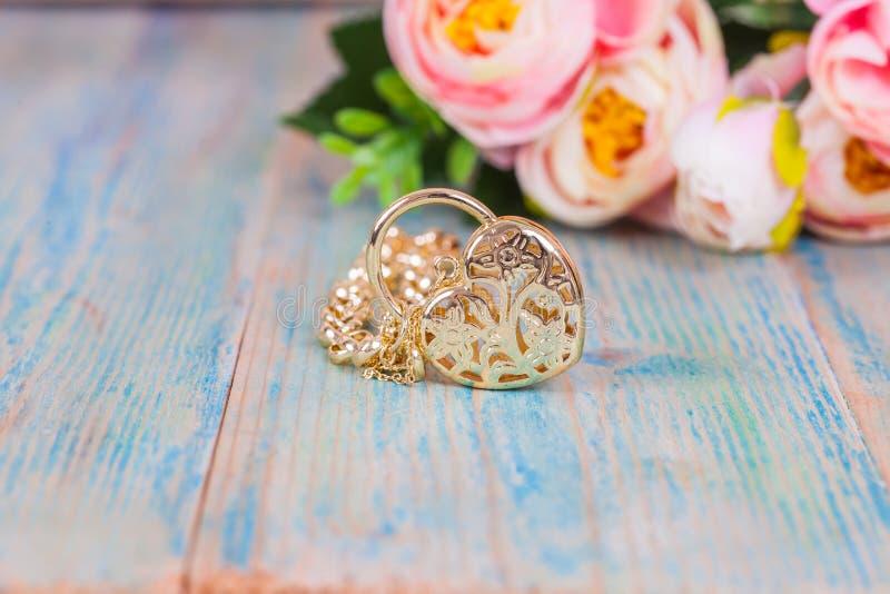 Guld- armband med hjärta på trä royaltyfri fotografi