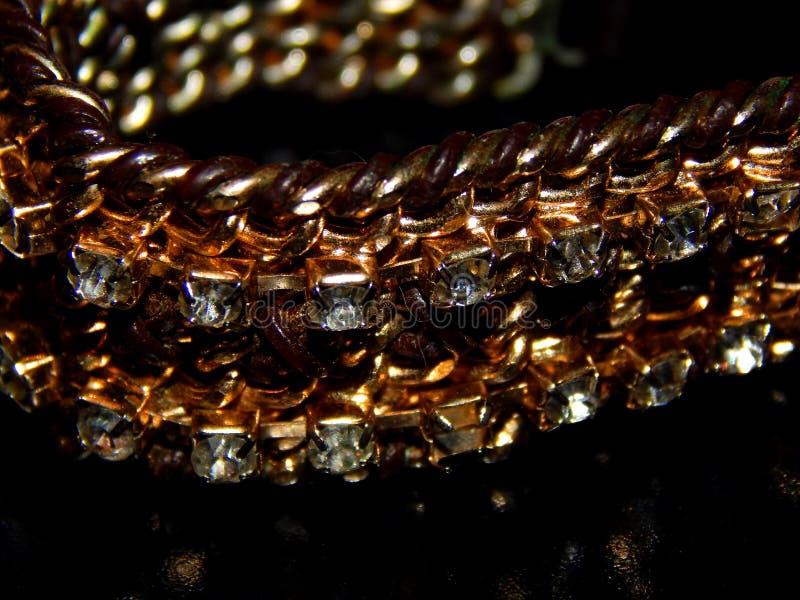 Guld- armband med stenar på en svart bakgrund fotografering för bildbyråer