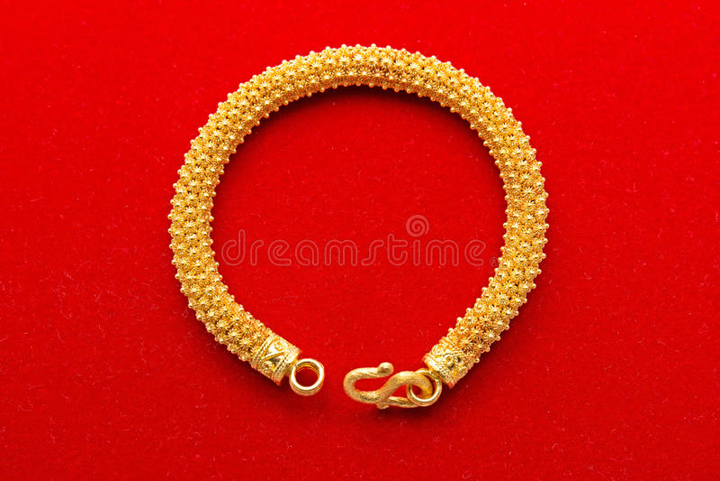 Guld- armband på röd bakgrund royaltyfri bild