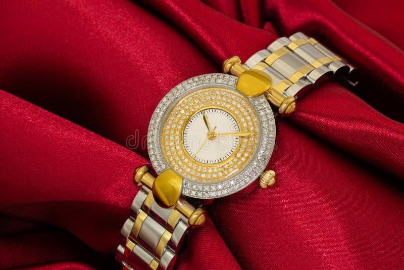 Guld- armbandsur på röd satäng fotografering för bildbyråer