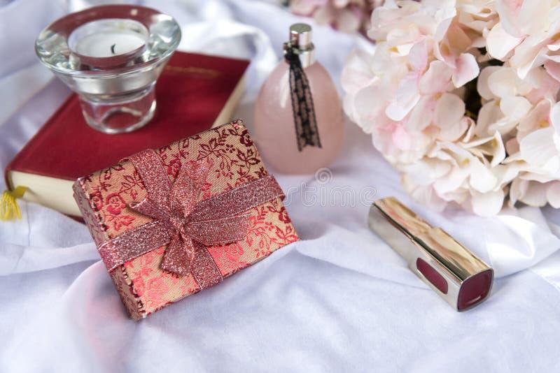 Guld- ask med röda blommor och en pilbåge, doftflaska, bok, stearinljus, rör med läppstift, vanlig hortensiablommor på vitt tyg royaltyfri foto