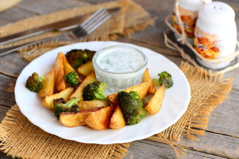 Guld- bakade potatisar och broccoli med sås på en platta och en trätabell Bakad potatis- och broccolireceptidé arkivfoto
