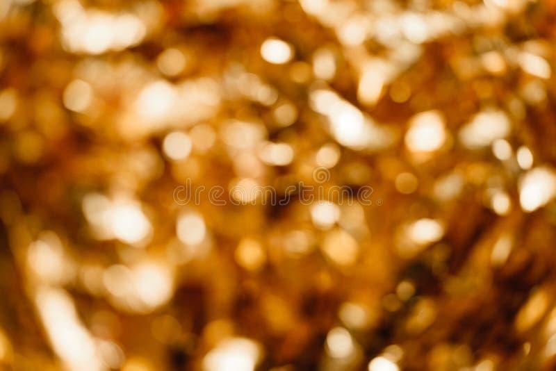 Guld- bakgrund ut ur fokus arkivfoton