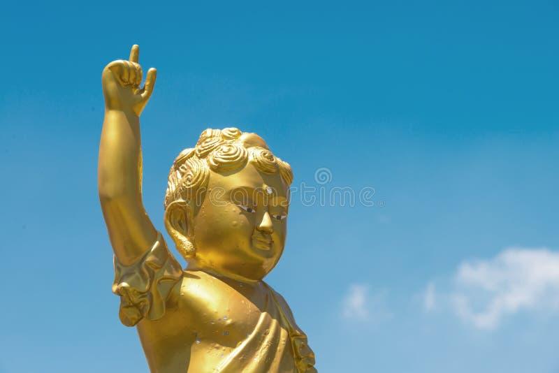 Guld- behandla som ett barn armen för Buddhastatylönelyften och peka pekfinger upp till b arkivbilder