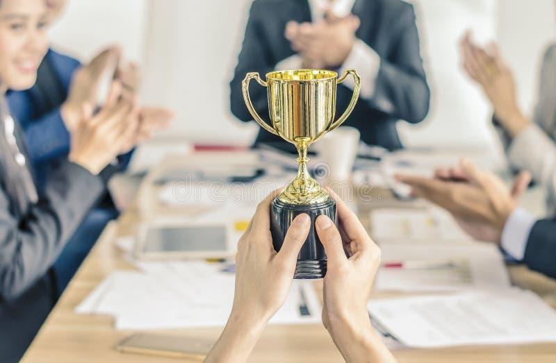 Guld- belönade trofé för vinnande affärslag, lyckligt samtycke för affärslag och lyckat affärslag royaltyfria foton
