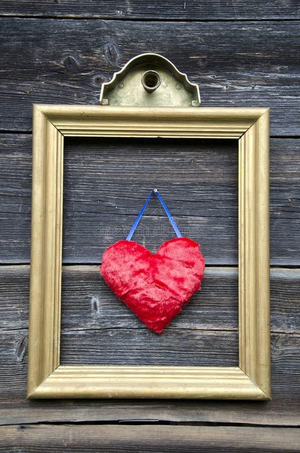 Guld- bildram för tappning med röd hjärta på väggen fotografering för bildbyråer