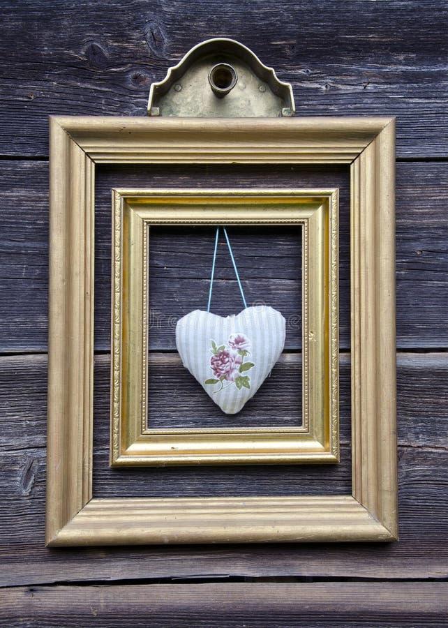Guld- bildram på trävägg- och torkdukehjärta royaltyfria foton