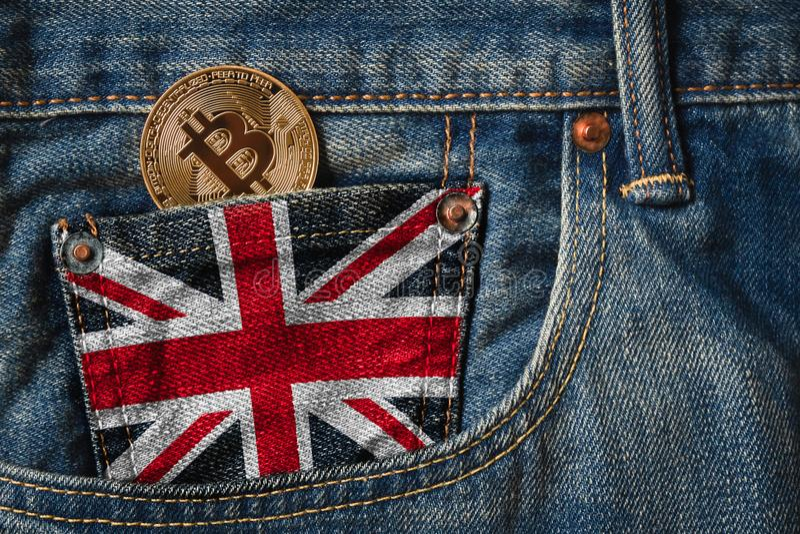 Guld- BITCOIN & x28; BTC& x29; cryptocurrency i facket av jeans med arkivfoton