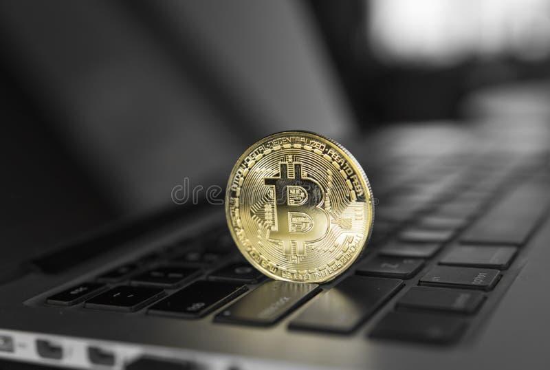 Guld- Bitcoin crypto mynt på ett bärbar datortangentbord Utbyte affär, reklamfilm Vinst från att bryta kryptavalutor arkivfoto