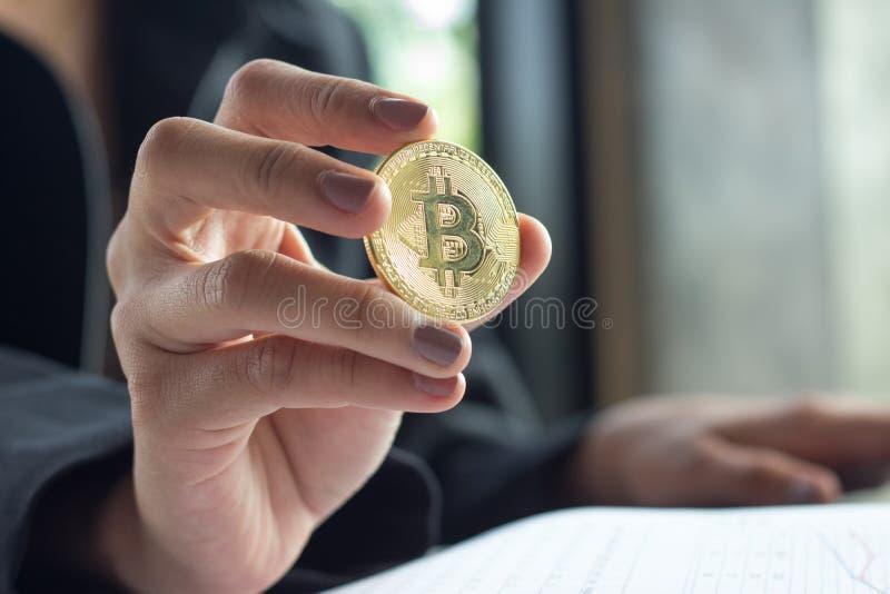 Guld- bitcoin förläggas på händer av den unga kvinnan för affären, Closeupbitcoin väljer fokus- och suddighetsbakgrund, utbyte royaltyfri bild