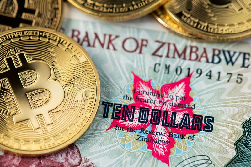 Guld- Bitcoin myntar nya faktiska pengar på slut för Zimbabwe hyperinflationsedel upp bild arkivfoton