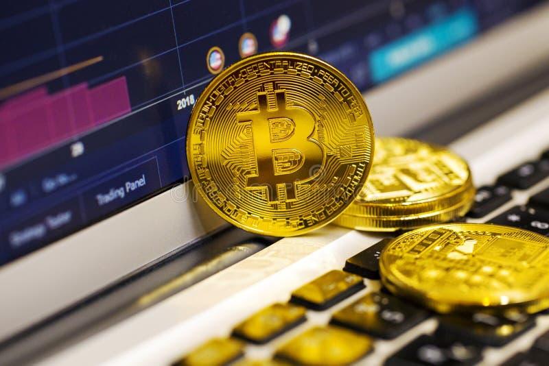 Guld- bitcoin på bärbar datortangentbordet på bakgrunden av materieldiagrammet arkivbilder
