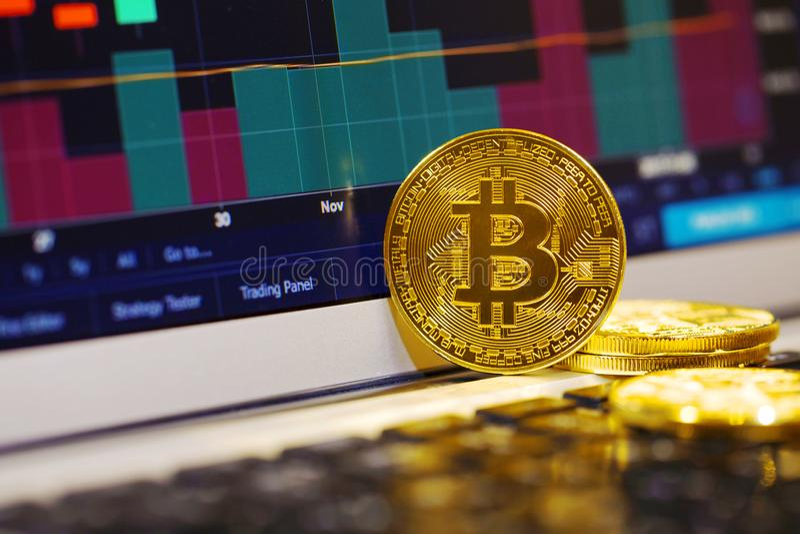 Guld- bitcoin på bärbar datortangentbordet på bakgrunden av materieldiagrammet royaltyfri bild