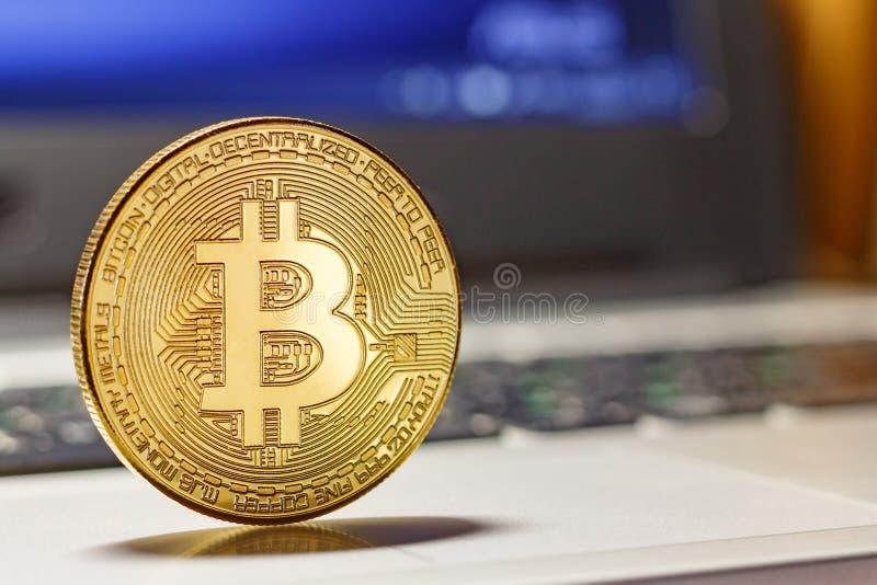 Guld- bitcoin på bärbar datortouchpadcloseupen Cryptocurrency faktiska pengar royaltyfri foto