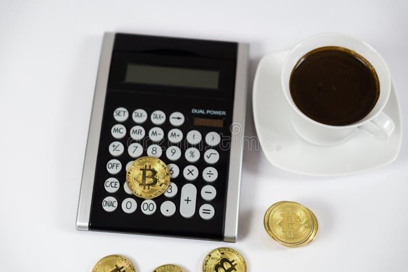 Guld- Bitcoin på den svarta räknemaskinen bredvid kaffe, cryptocurrencybegrepp royaltyfria bilder