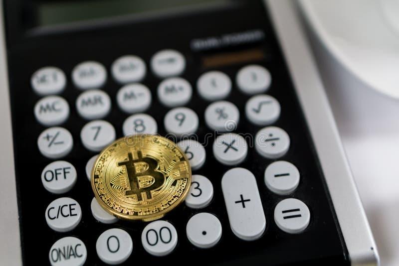 Guld- Bitcoin på den svarta räknemaskinen, cryptocurrencybegrepp royaltyfri foto