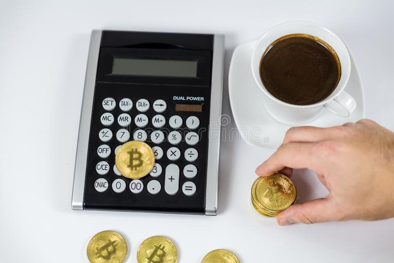 Guld- Bitcoin som rymms av handen på den svarta räknemaskinen bredvid kaffe, cryptocurrencybegrepp royaltyfri foto