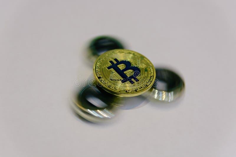Guld- bitcoinlögn på spinnare på den glass tabellcloseupen royaltyfria foton